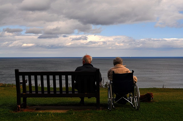 Senior couple with one sitting in a wheelchair