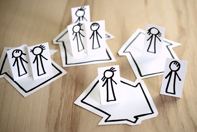 Paper cut of people standing on their houses