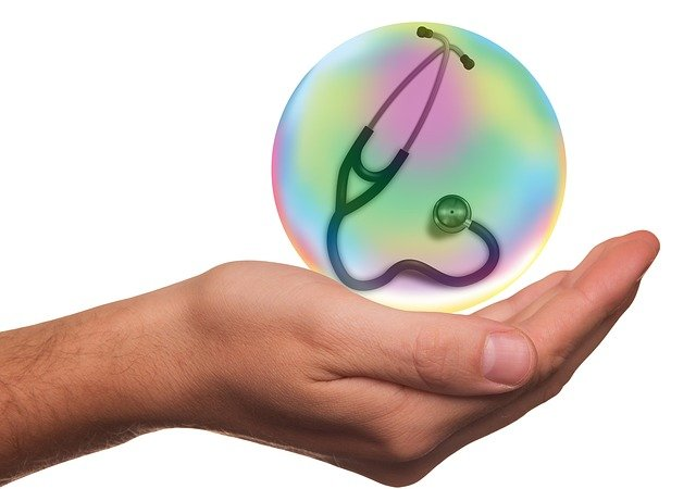 Hand holding a bubble with a stethoscope in it, health insurance