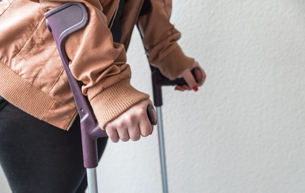 closeup of a person walks relying on walking sticks