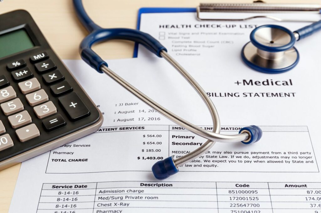 Medical billing statement, calculator, and a stethoscope